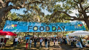 photo of Food Day banner and people entering a park